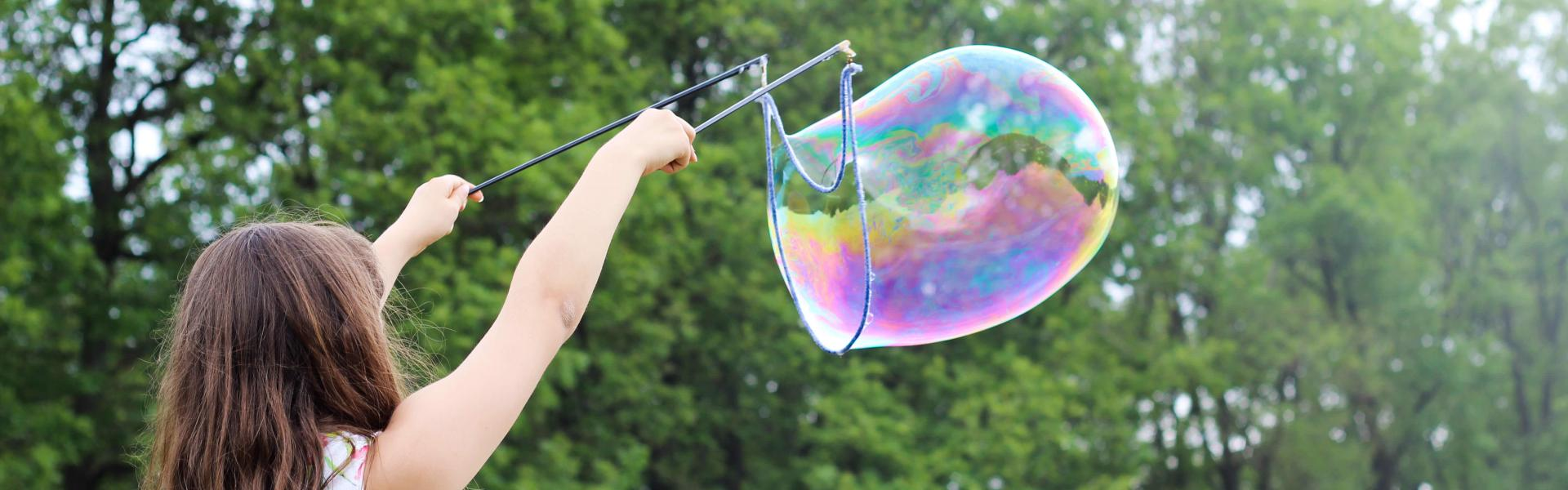 A young girl making large bubbles with a wand.