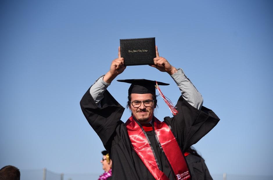 An LBCC student in a graduation cap & gown.