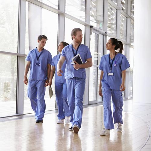 Health care professionals walking down a hallway.
