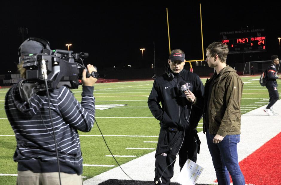 Sports reporter and crew on the football field.