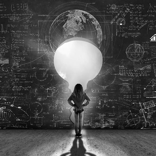 A girl standing in front of a key wall of Math